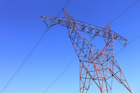 on an electricity pylon against blue sky for a renewable electricity or nuclear photo