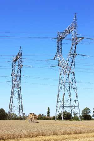 npp: electric pylon on a field with a combine in a field of wheat