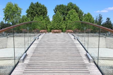glazing: a pedestrian bridge over a river in a city in bloom Stock Photo