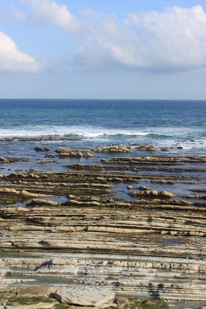 vague: rocks and an ocean at low tide under a blue sky