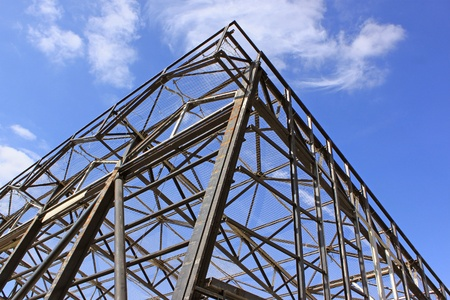 steel beam: a metal frame with safety net against a background of blue sky with clouds Stock Photo