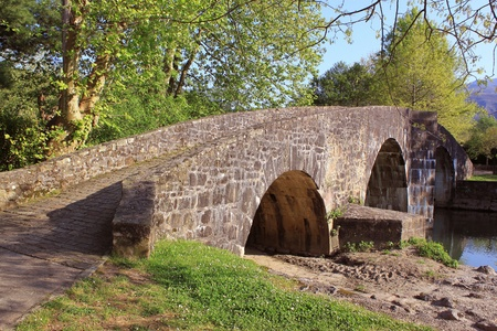 panorama of an ancient bridge over water in a landscape of nature Stock Photo