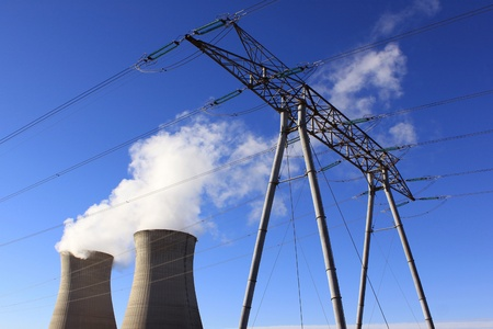 Chimneys of a nuclear power plant with a pylon for renewable energy on blue sky background