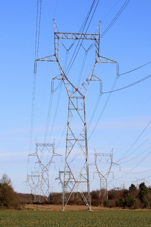 A row of electricity pylons in a field for a nuclear power