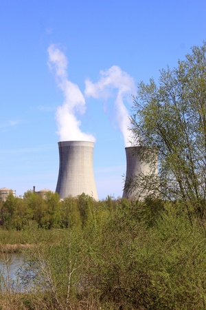 photo of an operating nuclear power plant on the banks of a river surrounded by trees photo