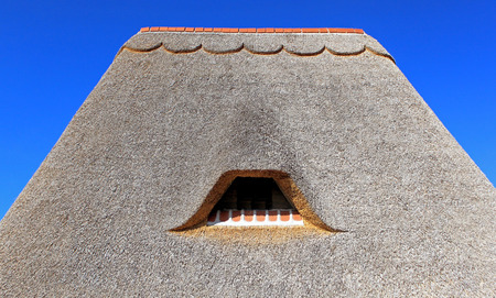 Cover thatch roof of a cottage on a blue sky background
