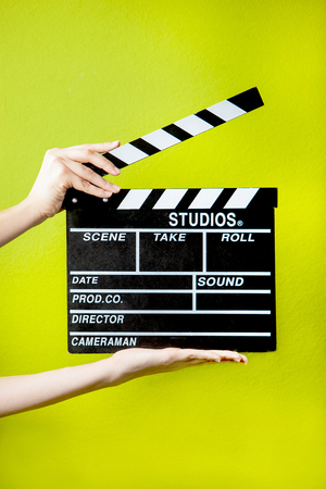 green background: Hands with clapperboard on a green background