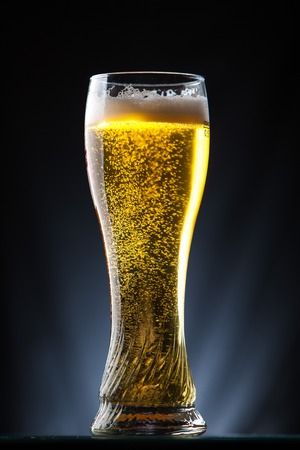tall glass: Tall glass of beer over a dark background lit yellow Stock Photo