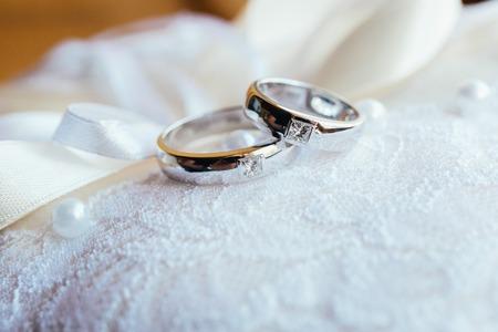 Vackra vigselringar på vit spets kudde Stockfoto