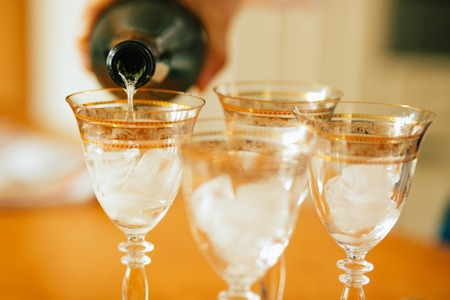 love gold: Pouring champagne into a glasses standing on table with waiter hand Stock Photo