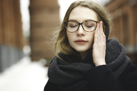 thoughful: Beautiful blonde young woman in glasses, in coat at street, in big city, waiting, dreaming, thoughful