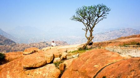 myst: Buddhist monk meditation at the top of mountain with singl tree Stock Photo