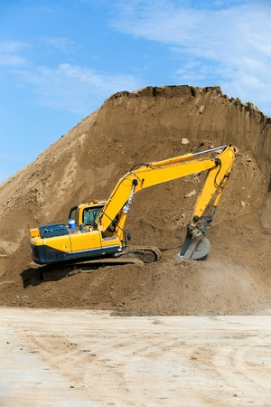 sand quarry: Yellow backhoe working digging in sand quarry Stock Photo