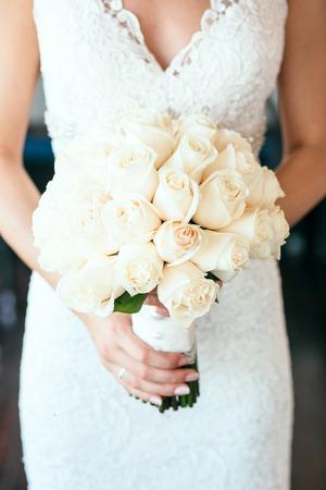 rosas blancas: Novia que sostiene el bouguet de flores hermosas