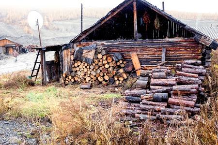 ethno: Beautiful ethno house with firewood at sunset Stock Photo