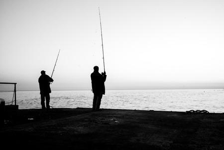 seashores: Two fishermen fishing rods on sea monochrome concept Stock Photo