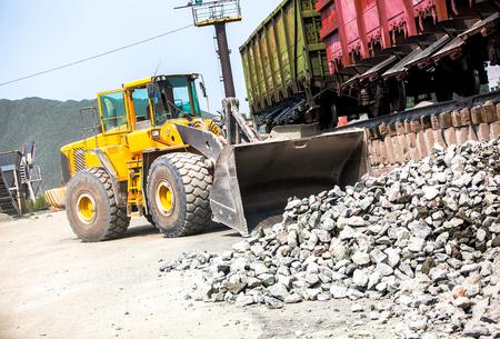 bulldozer: Yellow bulldozer working in stone granite quarry with train