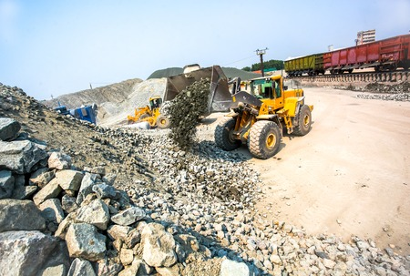sand quarry: Yellow bulldozer working in stone granite quarry with train