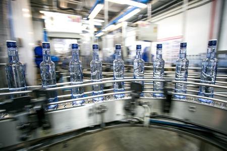 Many bottles on conveyor belt in factory, production of russian traditional alcohol drink vodka Foto de archivo