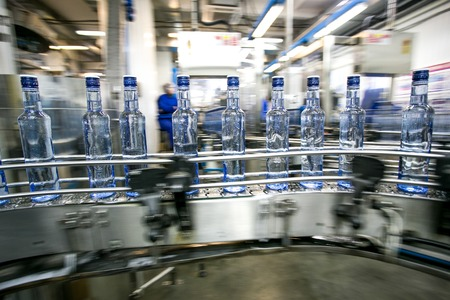 Many bottles on conveyor belt in factory, production of russian traditional alcohol drink vodka 스톡 콘텐츠