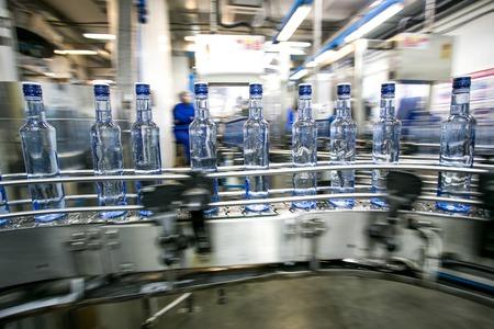 Muchas botellas en la banda transportadora en la fábrica, la producción de vodka ruso tradicional bebida de alcohol Foto de archivo