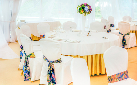 shoestring: wedding decoration of  white round tables and chairs with colorful elements of decor with  violet and green flower composition in shoestring vase