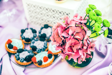 bouqet: soft focused assorted tarts and cupcakes with berries and  flower bouqet of  green chrysanthemum and  pink hydrangea on the violet tablecloth and white background
