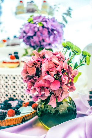 bouqet: flower bouqet of  green chrysanthemum and  pink hydrangea on the violet tablecloth and white backgroun with the soft focused assorted tarts and cupcakes with berries