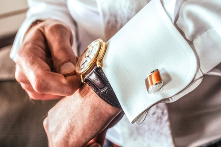 Man set the clock going, check time, brown wristlet, perfect white shirt and cuff-links