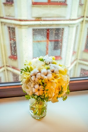 window sill: Bright yellow-white peony and cotton bouqet on the window sill on the rainy background