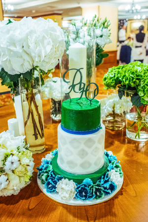 rhomb: Green and white wedding cake with the rhomb decoration  and blue-white flower decoration on the wooden table