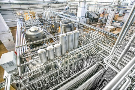 Large tanks and many shiny tubes plan view in the milk factory 写真素材