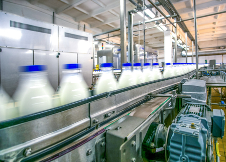 Milk production on line at the factory bottles with milk product in motion focused on conveyer details