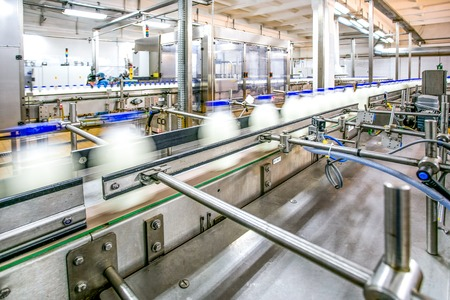 Milk production on line at the factory bottles with milk product in motion focused on conveyer details and stainless steel details and workers as background