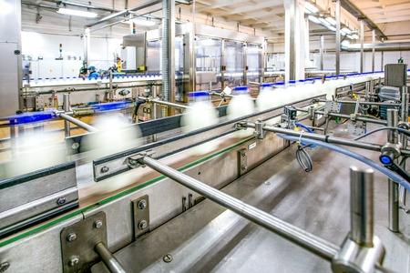 La production de lait en ligne sur les bouteilles d'usine avec un produit laitier en mouvement axé sur les détails de convoyage et des détails en acier inoxydable et des travailleurs comme arrière-plan Banque d'images - 53401429