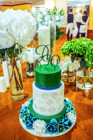 rhomb: Close-up green and white wedding cake with the rhomb decoration  and blue-white flower decoration on the wooden table Stock Photo