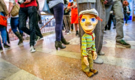 blue eyes: colorful man marionette at public place with grey hat and blue eyes and red hairs