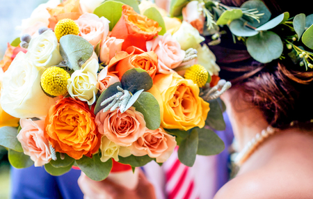 bouqet: Bright colorful wedding flower bouqet with blurred bridal and groom at background