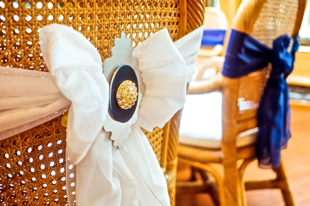 wedding chairs: Wooden wedding chairs decorated with white bows Stock Photo