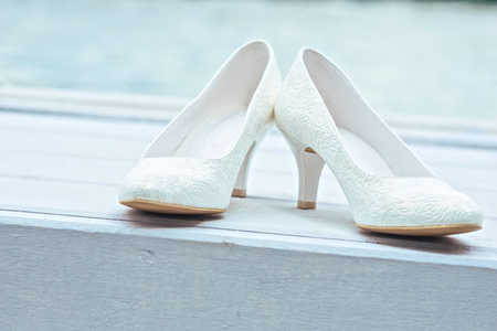 preperation: white wedding shoes on white wooden background under sun Stock Photo