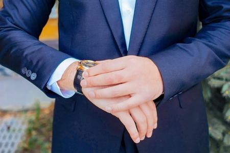 punctual: El hombre de negocios mira su reloj con la camisa blanca y traje