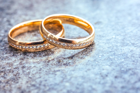 diamond rings: Wedding gold diamond rings on gray stone background