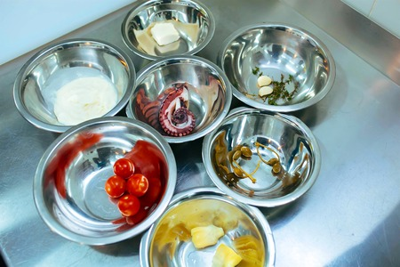 caper: Ingredients separately served in stainless bowls- octopus, tomato cherry, caper