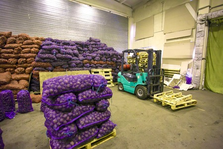 Bags and crates of potato in storage house with forklift truck   and palletes inside at yhe factiry