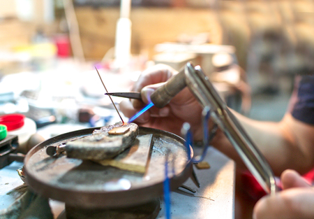 brazing: Focused brazing in progress for metal details at jewelry  workshop Stock Photo