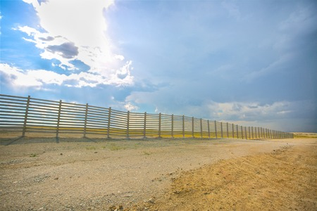 cattle wire: wooden fence in the sandy desert with blue sky