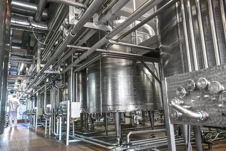 Dairy product factory inside with pipes and tanks Archivio Fotografico