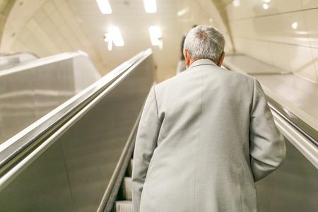 escalating: Old man escalating ahead on an escalator in the underground.