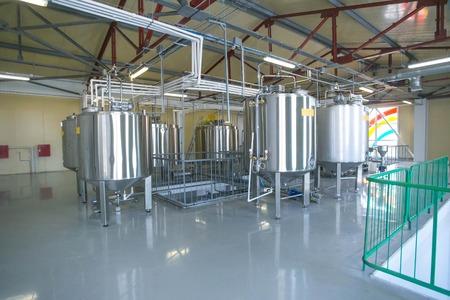Tank met vloeibaar in de fabriek van zuivelproduct houden temperatuur in het magazijn, hal Stockfoto