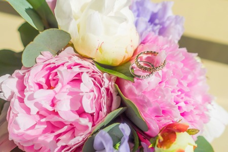 bouqet: Close up wedding rings on flowers bouqet consist of white and pink peonies